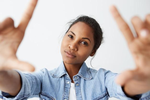 Feche acima do tiro do modelo encantador de brunetteafro-american encantador com pele escura saudável com sorriso fraco, posando dentro de casa contra a parede em branco, vestindo camisa jeans.