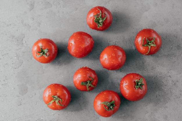 Feche acima do tiro dos tomates vermelhos da herança enchidos com gotas da água contra o fundo cinzento.
