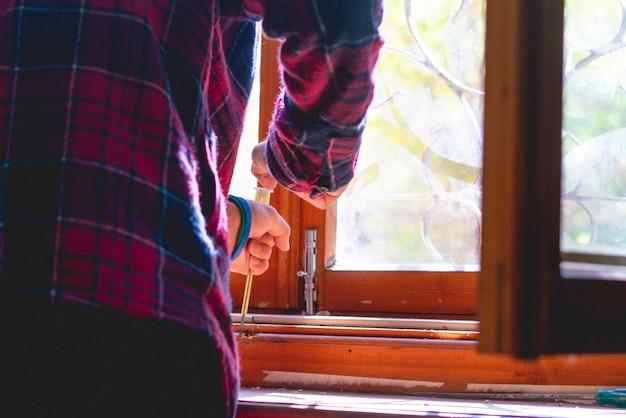 Feche acima do trabalhador masculino que repara a janela velha de madeira em casa