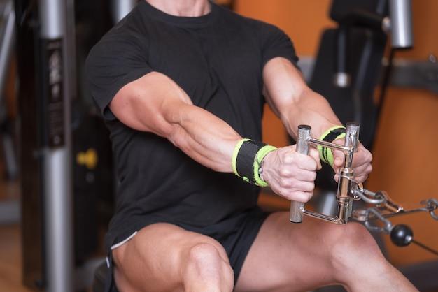 Feche acima do treinamento do homem forte no trem superior dorsal da ginástica.