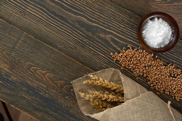 Feche acima do trigo e do painço de sal no cozimento do pão do copyspace da tabela que cozinha o conceito natural orgânico dos alimentos do supermercado da padaria do produto delicioso saboroso da receita.