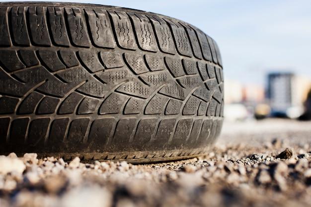 Feche acima do único pneu no asfalto
