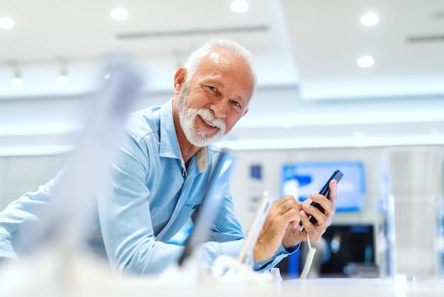 Feche acima do velho homem barbudo caucasiano tentando telefone inteligente enquanto olha para a câmera e inclinando-se sobre o carrinho na loja de tecnologia.