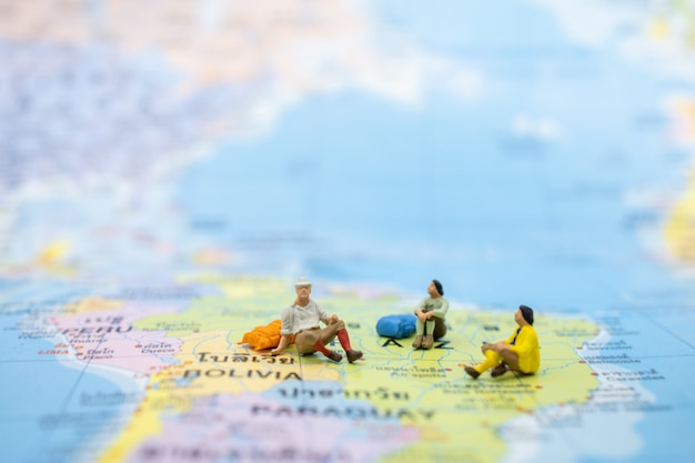 Feche acima do viajante do grupo com a trouxa que senta-se no mapa colorido.