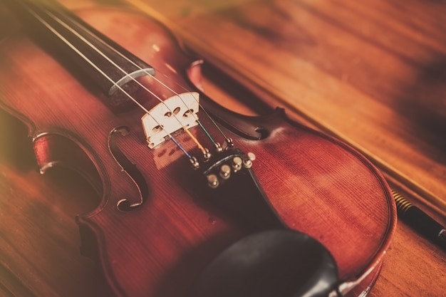 Feche acima do violino no fundo de madeira no estilo do vintage.