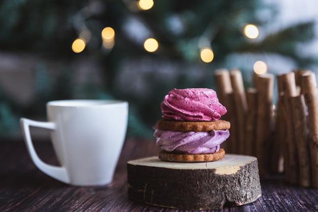 Feche acima do zéfiro cor-de-rosa e roxo caseiro ou do marshmallow no açúcar em pó com a caneca branca em de madeira com bokeh abstrato. groselha preta, marshmallows de mirtilo.