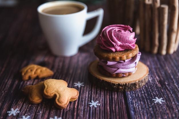 Feche acima do zéfiro cor-de-rosa e roxo caseiro ou do marshmallow no açúcar em pó com a caneca branca em de madeira. groselha preta, marshmallows de mirtilo.