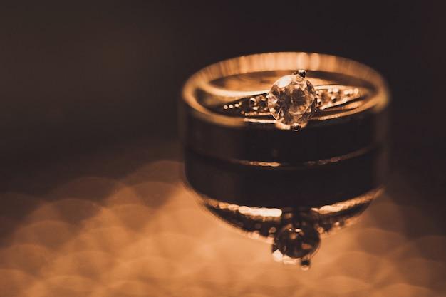 Feche acima dos anéis de casamento do diamante com foco seletivo