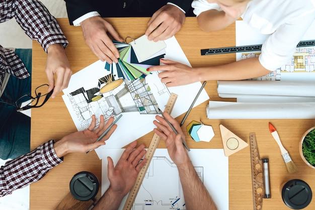 Feche acima dos arquitetos de designers, discutindo o projeto.