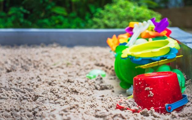 Feche acima dos brinquedos coloridos no campo de jogos da areia.
