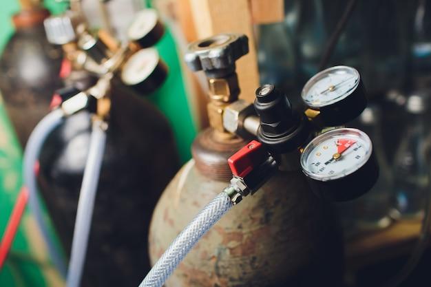 Feche acima dos calibres e da válvula no cilindro de gás nitrogênio velho no laboratório.