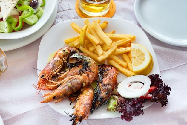 Feche acima dos camarões grandes da grade do tamanho com batata, os vegetais e o limão fritados, tempo do almoço no restaurante.