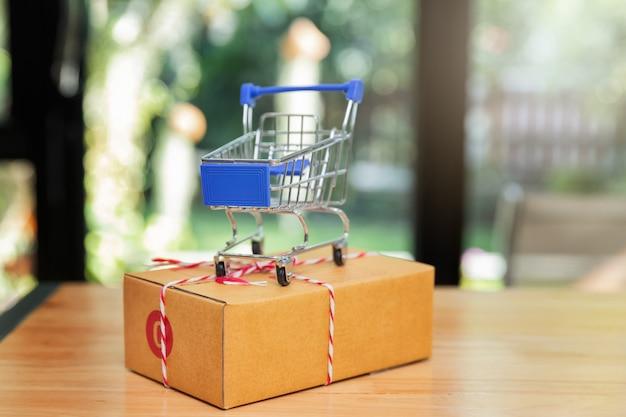 Feche acima dos carrinhos de compras diminutos na caixa do pacote.