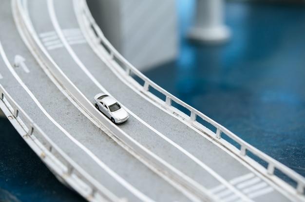 Feche acima dos carros pequenos modelo na passagem superior, conceitos do tráfego.