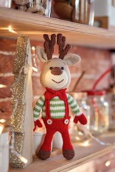Feche acima dos cervos de amigurumi de brinquedo em suéter listrado e elegante gravata borboleta vermelha fica na prateleira de madeira perto da árvore de natal decorada e luzes de natal.