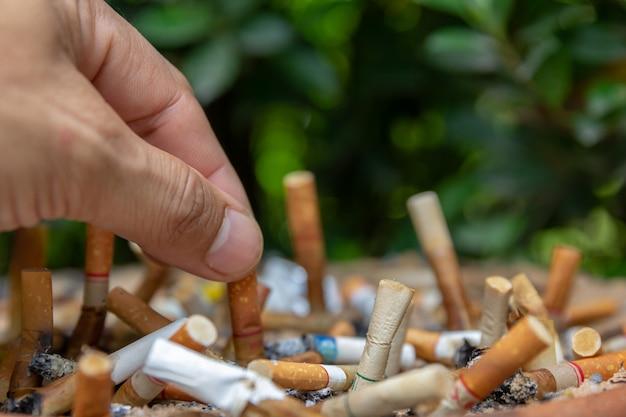Feche acima dos cigarros da pessoa do homem da mão para o suporte de fumo na área da zona de fumo.
