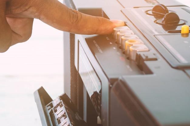 Feche acima dos dedos para jogar o leitor de cassetes de rádio, estilo do vintage.