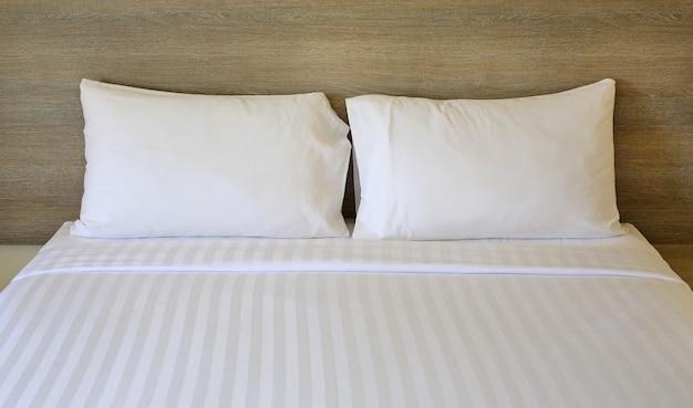 Feche acima dos descansos brancos na cama no hotel.