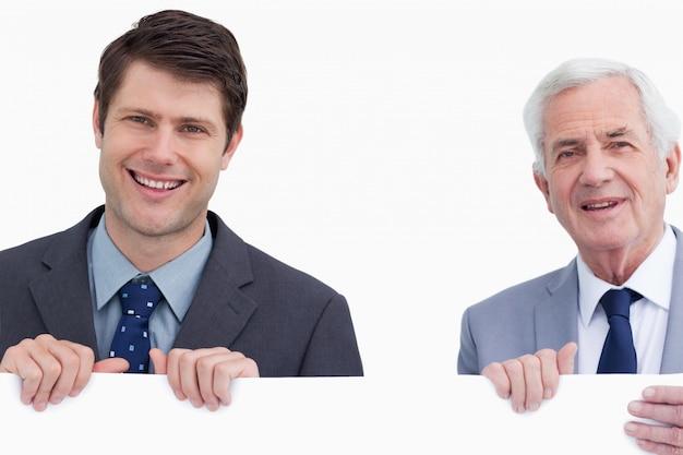 Feche acima dos empresários sorridentes que prendem o sinal em branco
