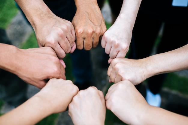 Feche acima dos estudantes que estão as mãos que fazem o gesto da colisão do punho.
