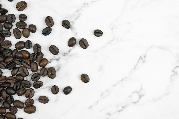 Feche acima dos feijões de café em um fundo de mármore do teste padrão com espaço da cópia. vista do topo.