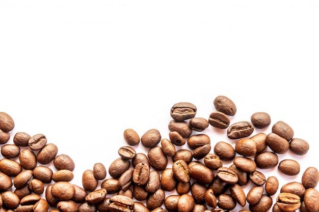 Feche acima dos feijões de café no fundo branco