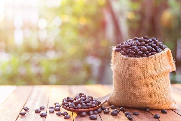Feche acima dos feijões de café roasted no saco pequeno na tabela de madeira.