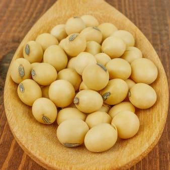 Feche acima dos feijões de soja macro na colher de pau