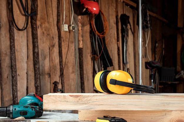 Feche acima dos fones de ouvido amarelos da construção em uma placa de madeira. construção, carpintaria.