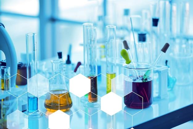 Feche acima dos frascos cônicos de vidro aberto, alinhados com líquidos coloridos dentro
