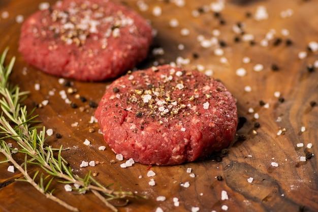 Feche acima dos hamburgueres triturados crus do bife handmade com sal e pimenta preta. fazenda de carne orgânica. fundo de madeira