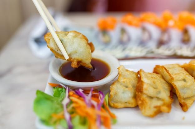 Feche acima dos hashis que apertam as bolinhas de massa do gyoza (gyoza japonês) que sentam-se em uma tabela de madeira rústica no restaurante chinês.