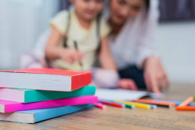 Feche acima dos livros no assoalho com mamã e miúdos. de volta à escola e à educação