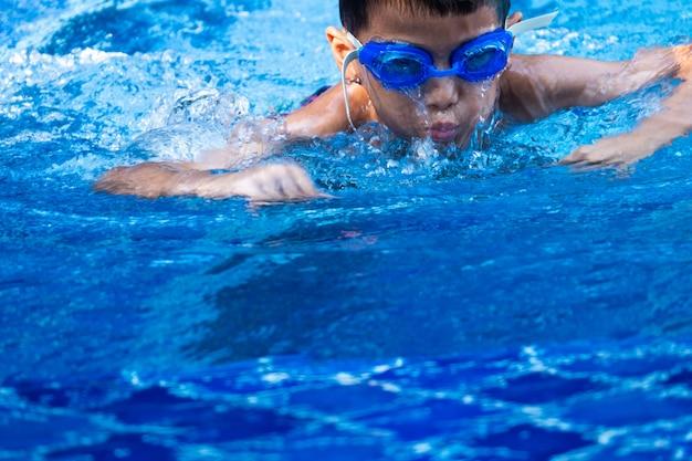 Feche acima dos mercadorias asiáticos do menino vidros azuis que mergulham e que nadam na piscina e na água de refrescamento azul.