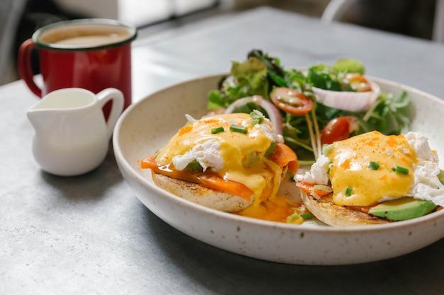 Feche acima dos ovos benedict com salmões e abacate.