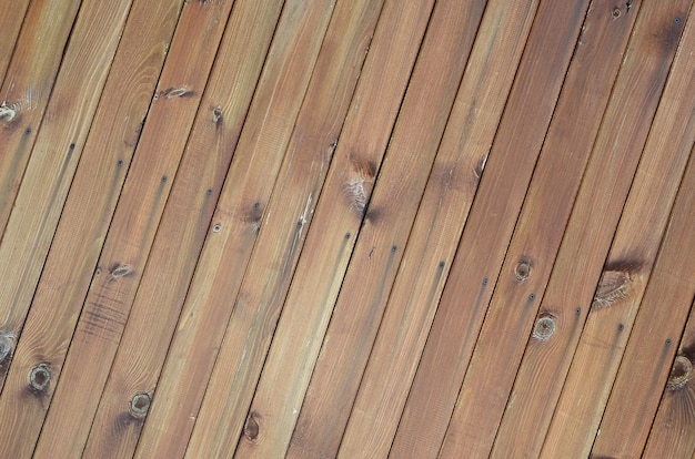 Feche acima dos painéis de madeira marrons da cerca. muitas pranchas de madeira verticais