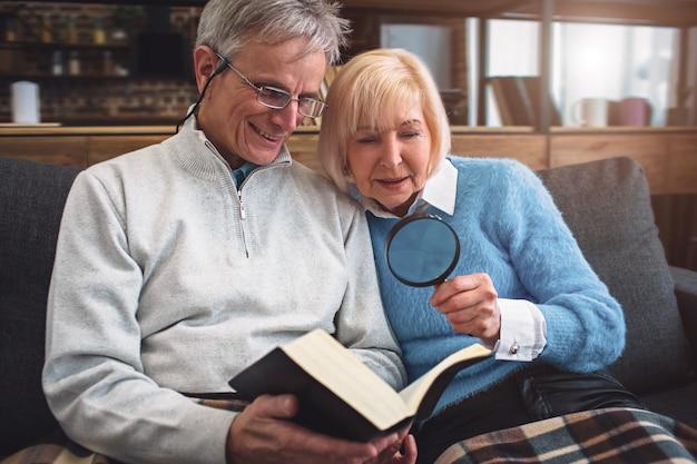 Feche acima dos pares velhos que leem um livro. ele está usando óculos para ler