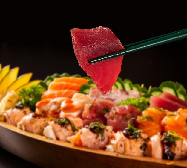 Feche acima dos peixes de atum no hashi com a combinação japonesa do alimento defocused no fundo preto.