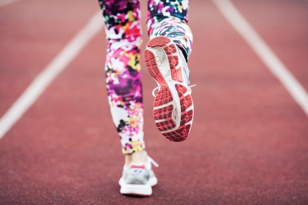 Feche acima dos pés das meninas nos sneakers e nas calças justas.