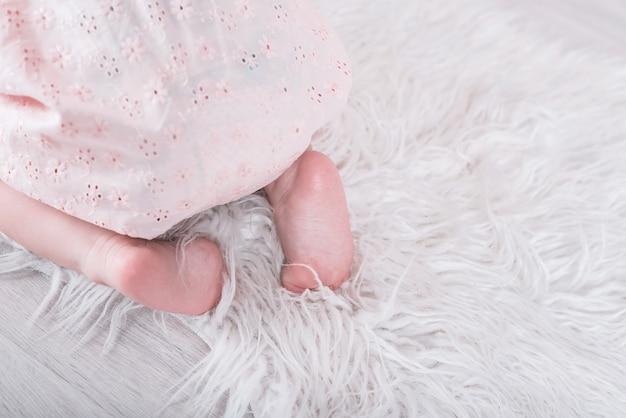 Feche acima dos pés desencapados encantadores do bebê no assoalho.