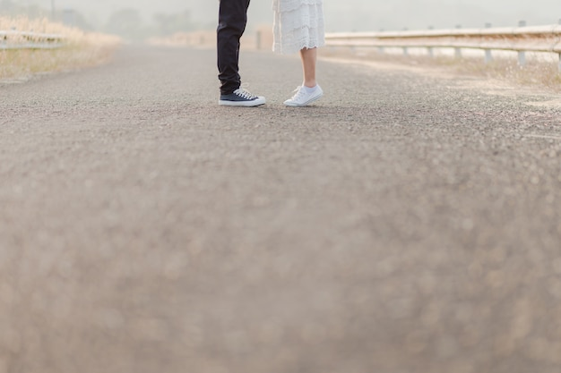 Feche acima dos pés e das caixas dos amantes que estão no meio da estrada.