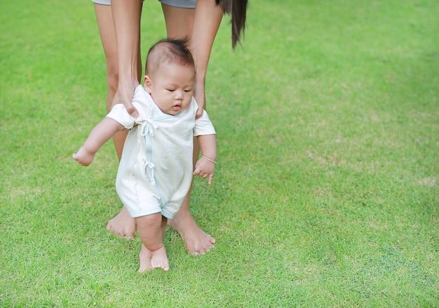 Feche acima dos pés infantis do bebê que aprendem andar com sua mãe na grama verde.