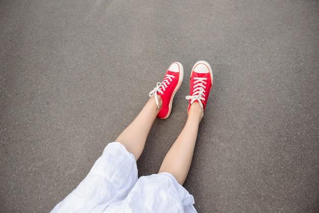 Feche acima dos pés nos keds vermelhos que encontram-se no asfalto.