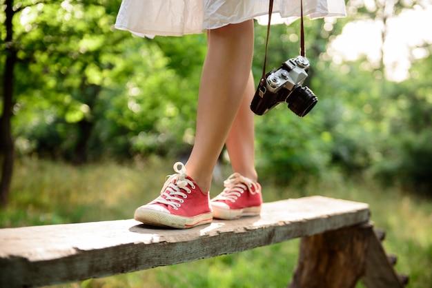 Feche acima dos pés nos keds vermelhos que steping na mesa.