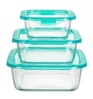 Feche acima dos recipientes de alimento de vidro isolados no branco