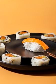 Feche acima dos rolos de sushi maki com nigiri em fundo amarelo