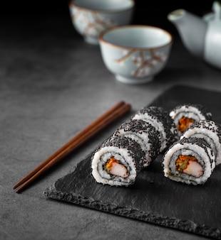 Feche acima dos rolos de sushi maki com sementes de gergelim preto