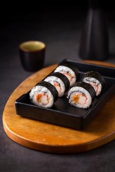 Feche acima dos rolos de sushi maki na ardósia preta