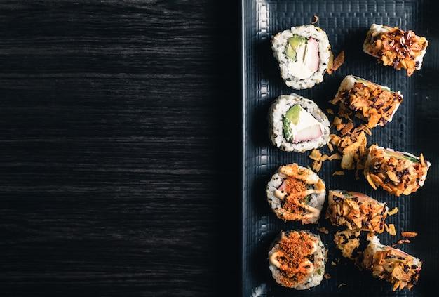 Feche acima dos rolos de sushi na bandeja preta. espaço da cópia