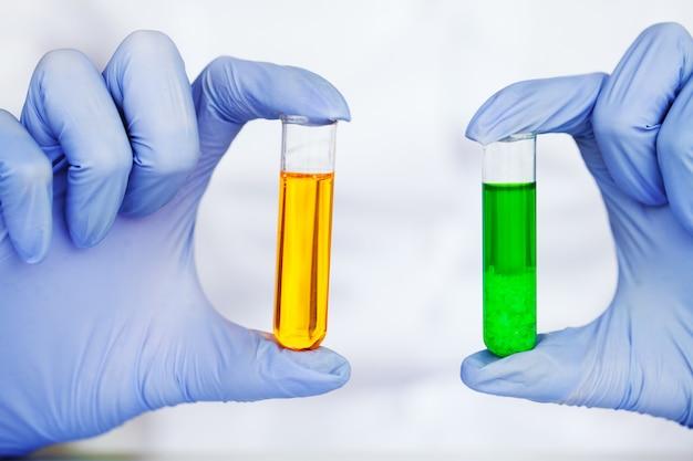 Feche acima dos tubos de ensaio de verificação do cientista no laboratório
